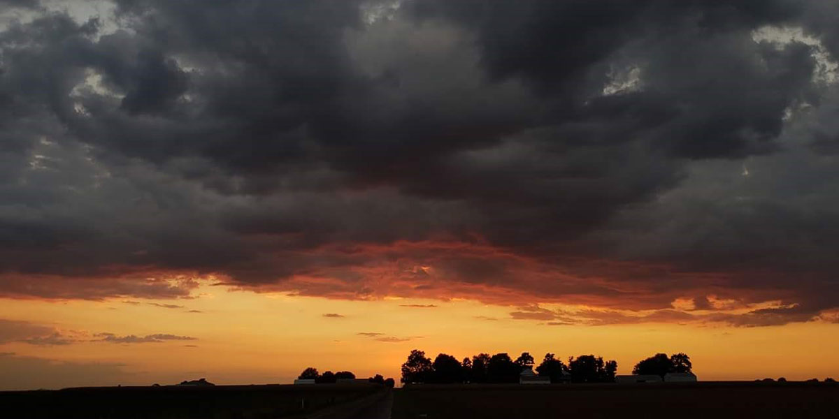 Storm clouds over the silhouette of a farm at sunset