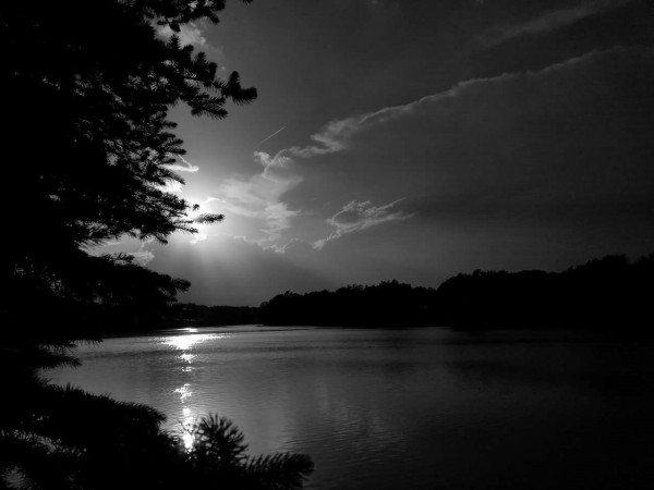 A black and white photo of a sunset over a lake